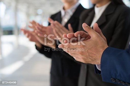 istock Three business people clap their hands to congratulate the signing of an agreement or contract between their firms, companies, enterprises. success, dealing, greeting and partner concept. 872449496