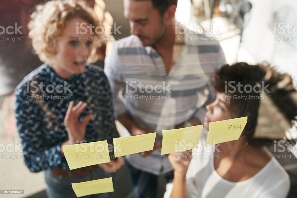 Three business people having a meeting at sticky note wall stock photo