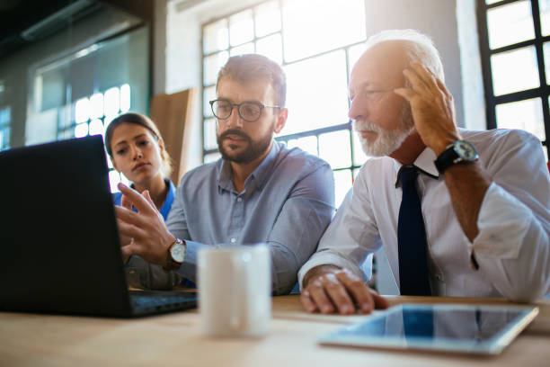 Three business people having a meeting at the modern office stock photo