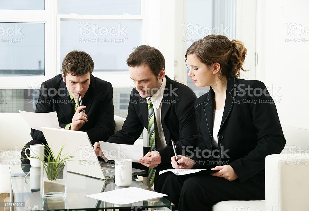 Drei Geschäftsleute in Anzügen gerafft am laptop Lizenzfreies stock-foto