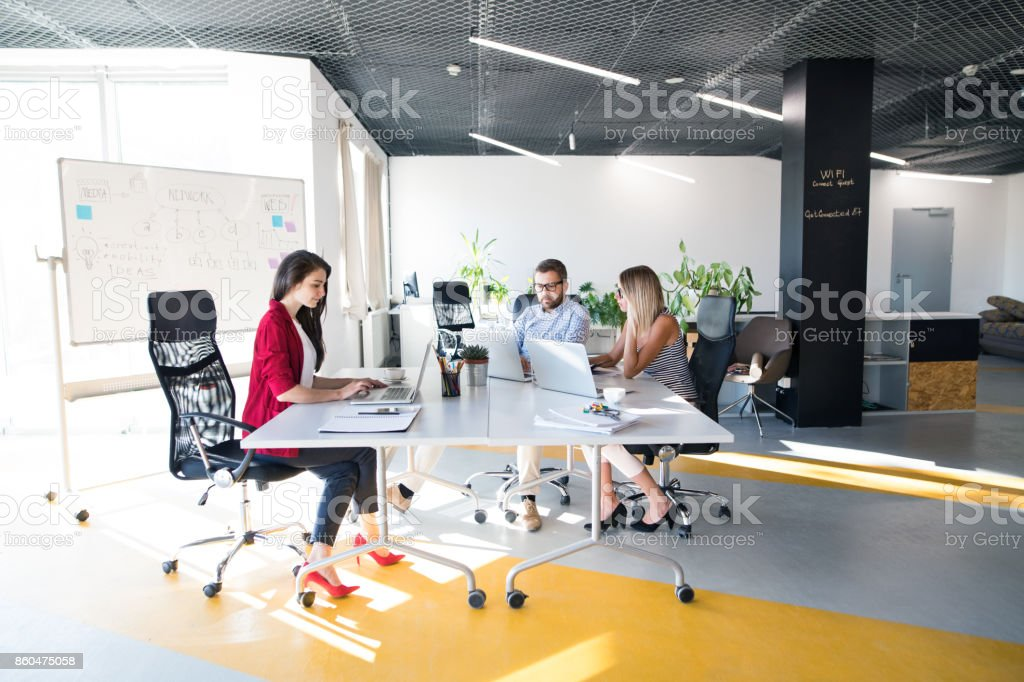Three business people in the office talking together. stock photo
