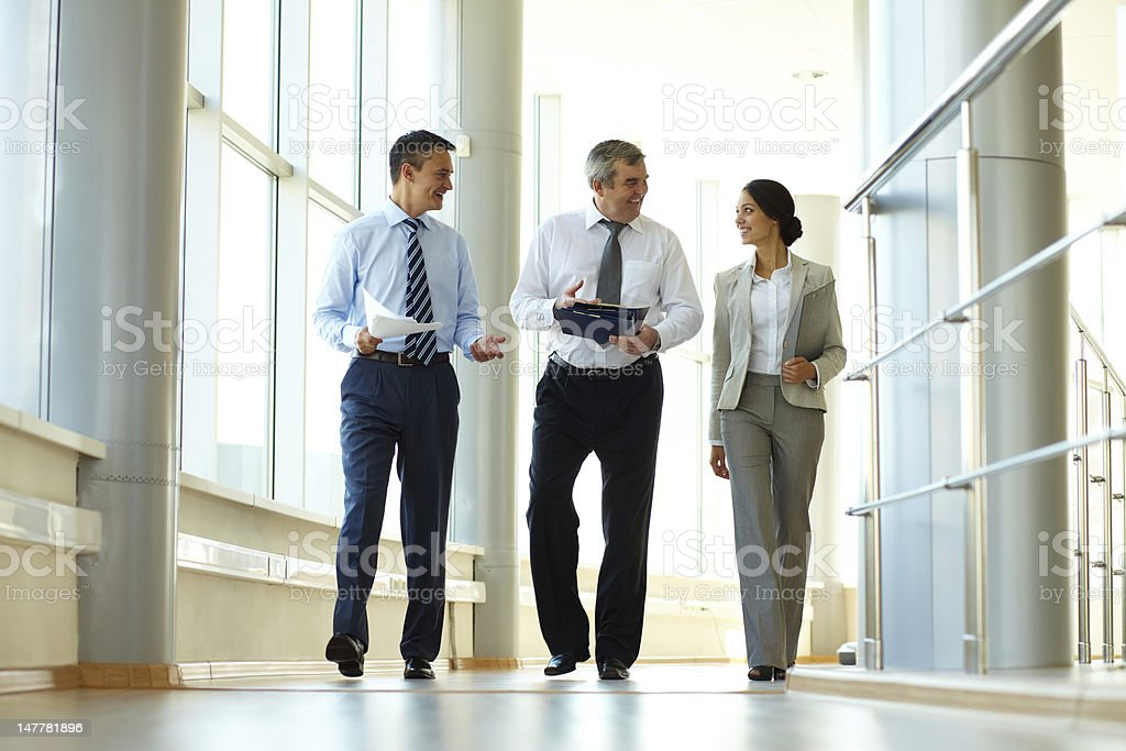 Confident business partners walking down in office building and...