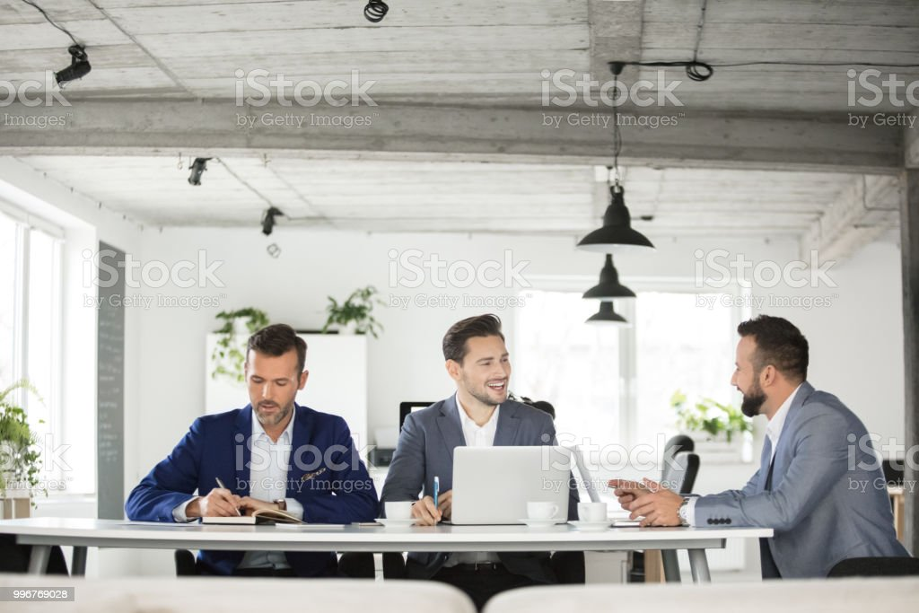 Three business people meeting office Three business people working together in office. Corporate professional having meeting in office. Adult Stock Photo
