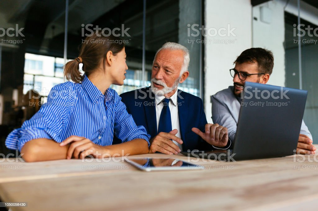 Three business people sitting and discussing work Group of business people having a meeting at the office Active Seniors Stock Photo