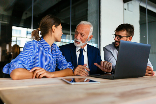 Three Business People Sitting And Discussing Work Stock Photo - Download Image Now