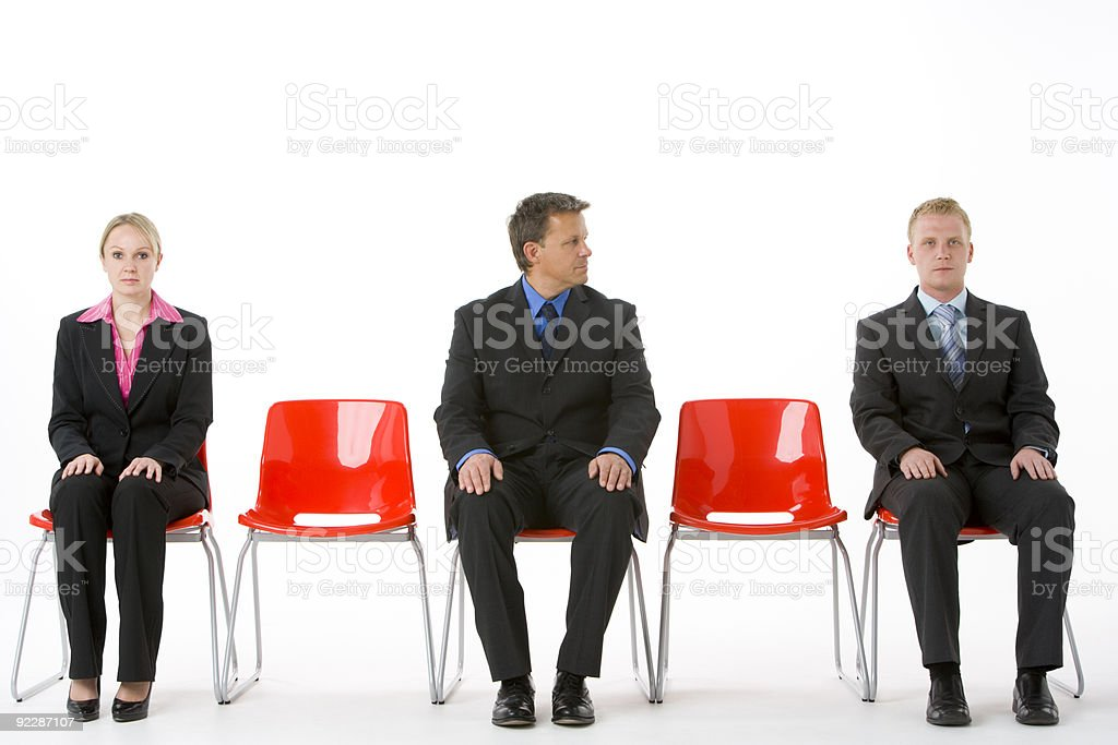 Three Business People Sitting On Red Plastic Seats royalty-free stock photo