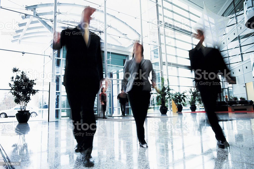 Three Business People Walking Quickly Though Office Entrance stock photo