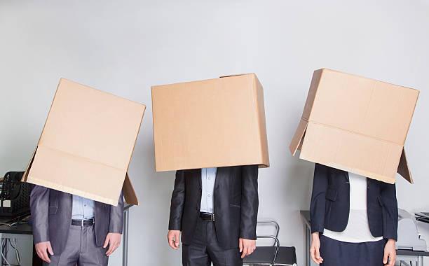 Drei Geschäftsleute mit Boxen auf Ihren Köpfen – Foto
