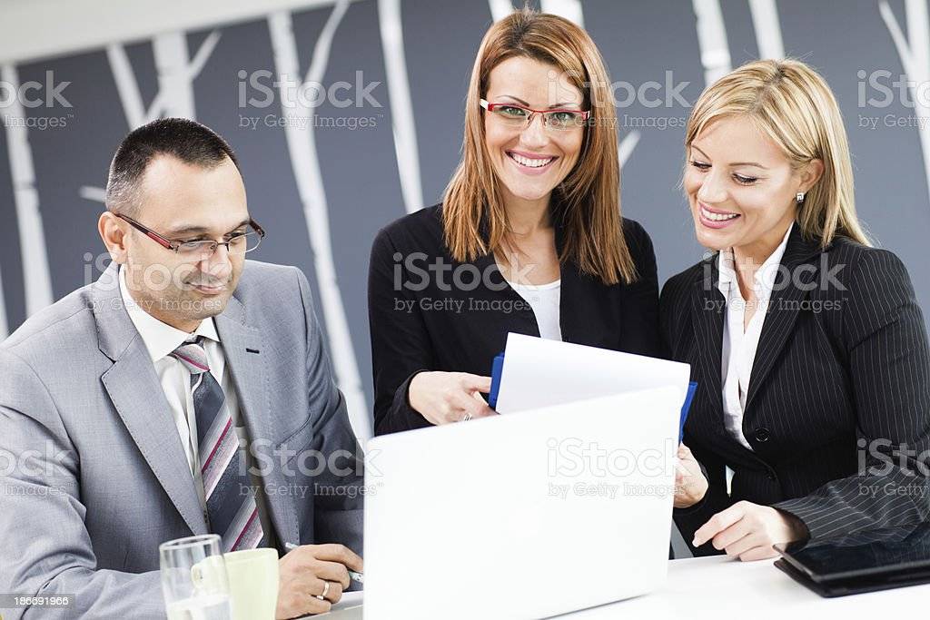 Three business people working in office on lap top royalty-free stock photo