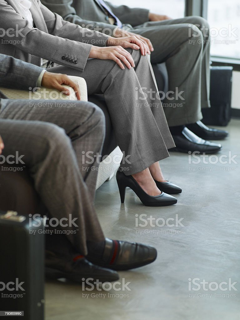 Three business people's legs in an office lobby royalty-free stock photo