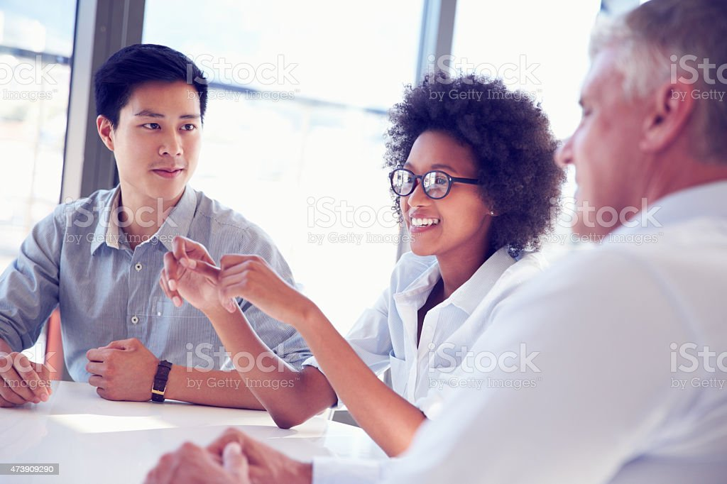 Three business professionals working and sharing ideas stock photo