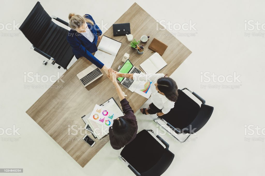 Three business woman discussing work on table in office, top view