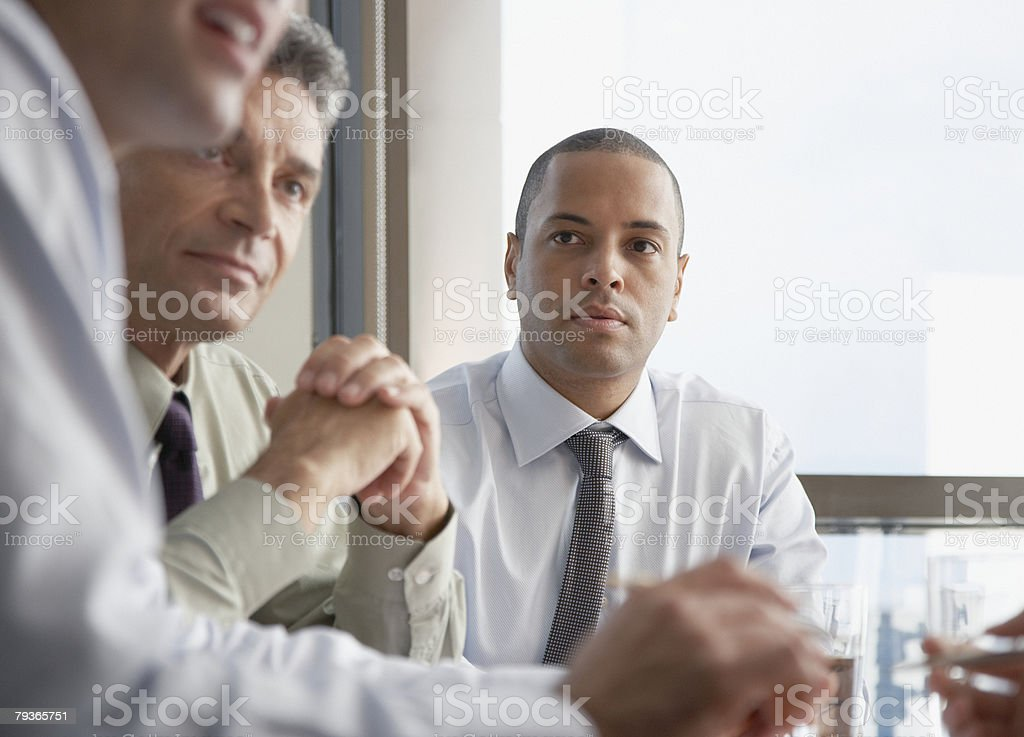 Three businessmen at a boardroom table royalty-free stock photo
