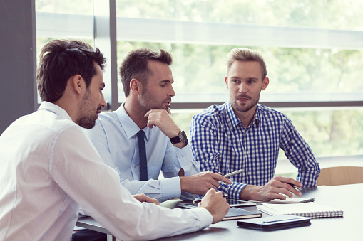 Three Businessmen Discussing In A Meeting Room Stock Photo - Download Image Now