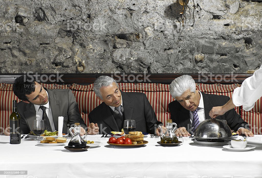 Three businessmen looking at dish being uncovered by waiter royalty-free stock photo