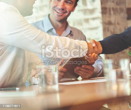859896852istockphoto Three businessmen meeting in a board room closing a deal. 1139771811