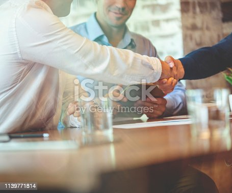 859896852istockphoto Three businessmen meeting in a board room closing a deal. 1139771814