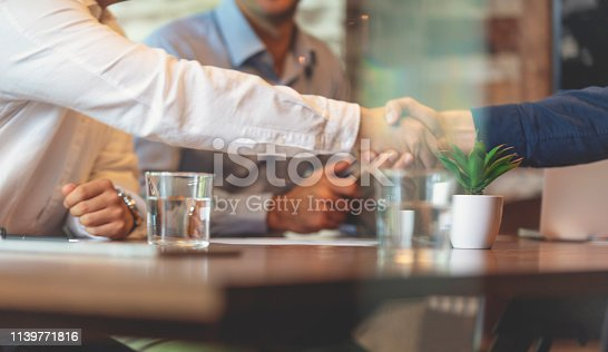 859896852istockphoto Three businessmen meeting in a board room closing a deal. 1139771816