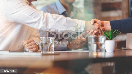 859896852istockphoto Three businessmen meeting in a board room closing a deal. 1139771817
