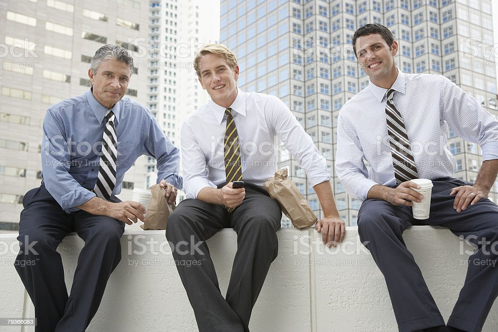 Three businessmen outdoors on a lunch break stock photo