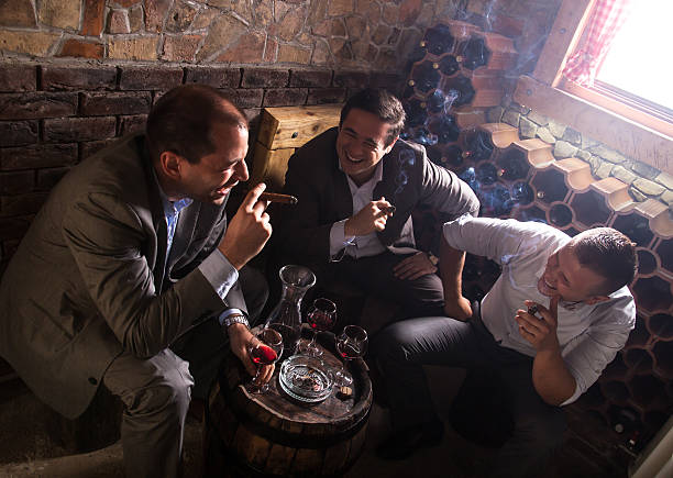 three businessmen resting after a hard day at work. - guy with cigar stockfoto's en -beelden