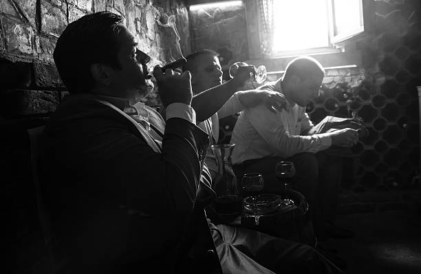 Three businessmen resting after a hard day at work. Three businessmen sitting in the wine cellar drinking wine and smoke cigar, resting after a hard day at work. Black and White. gangster stock pictures, royalty-free photos & images