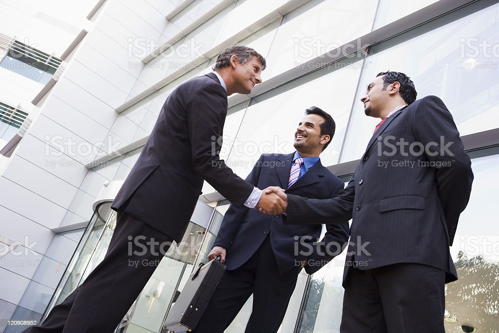 Three businessmen shaking hands outside an office building stock photo