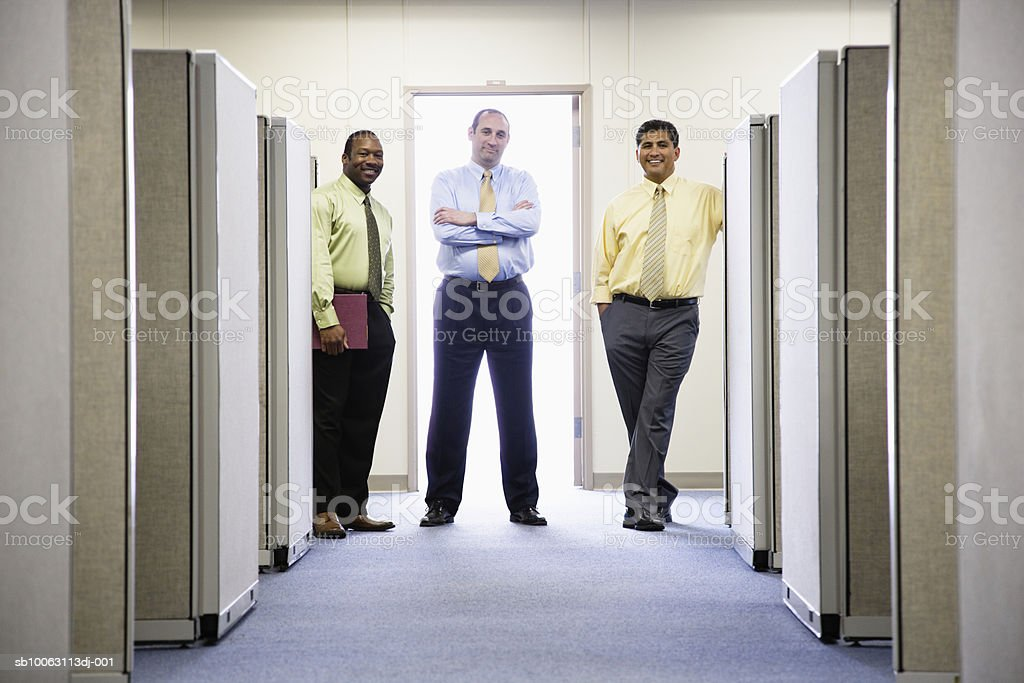Three businessmen standing between cubicle in office, smiling, portrait royalty-free stock photo