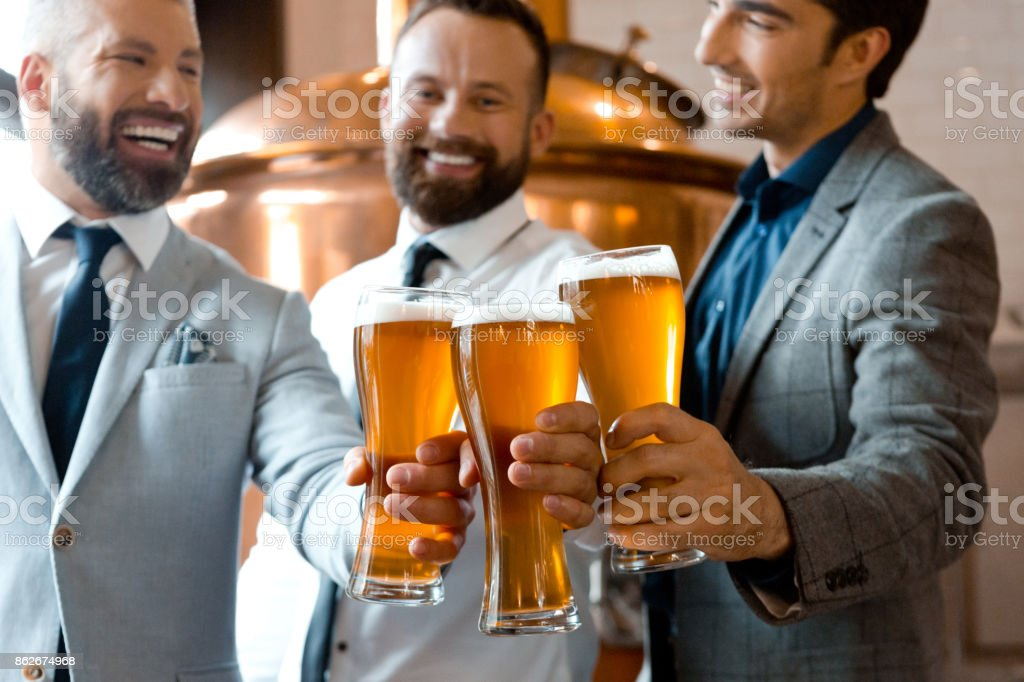 Three businessmen toasting with beer in micro brewery Three happy businessmen toasting with beer in microbrewery. Adult Stock Photo