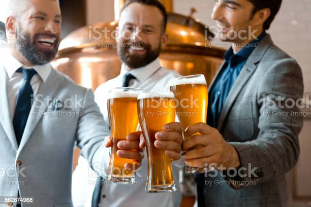 Three Businessmen Toasting With Beer In Micro Brewery Stock Photo - Download Image Now