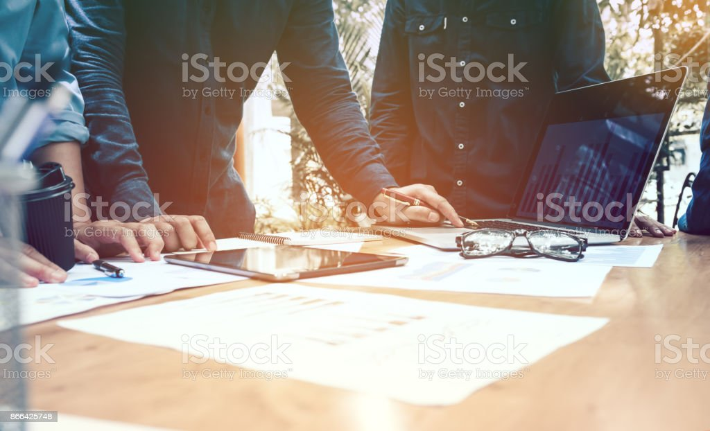 Three businessmen working on laptop computer with documents and paperwork scattered around and digital tablet on desk. stock photo