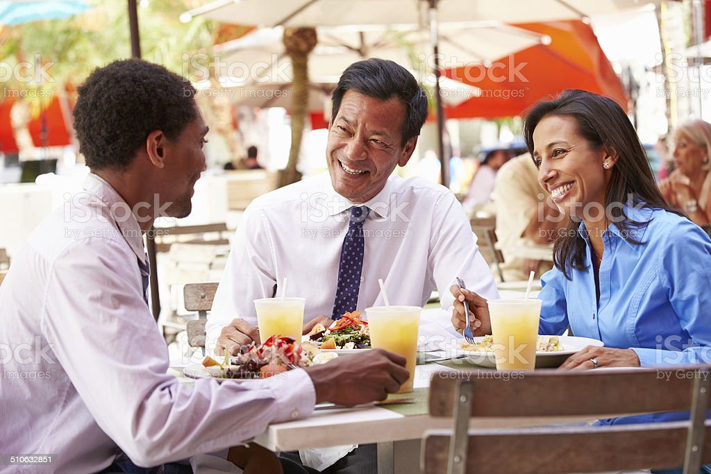 Three Businesspeople Having Meeting In Outdoor Restaurant stock photo