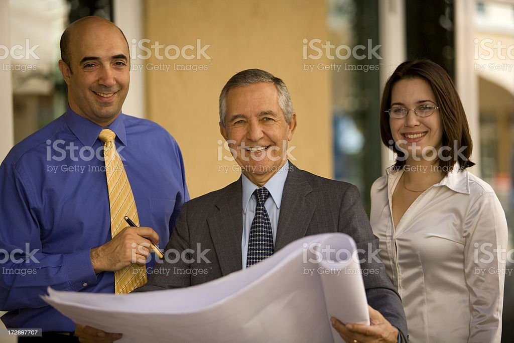 Three businesspeople holding architectural plans royalty-free stock photo