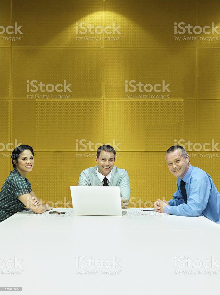 Three businesspeople in a boardroom with a laptop royalty-free stock photo