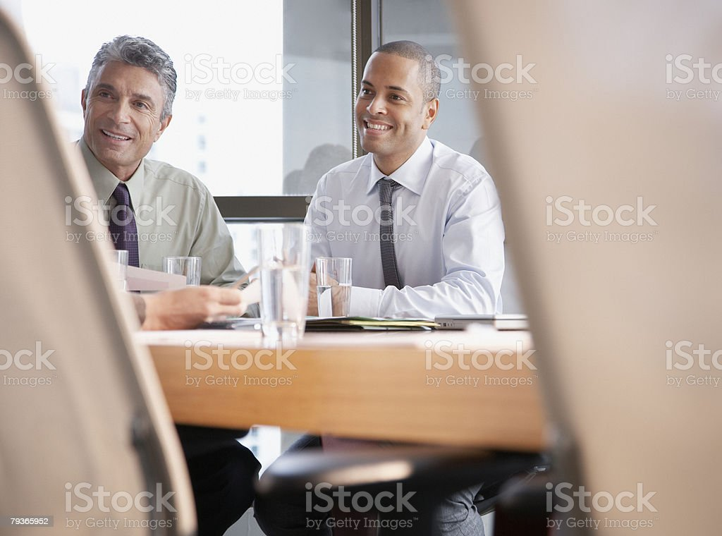 Three businesspeople in a boardroom with one off camera 免版稅 stock photo