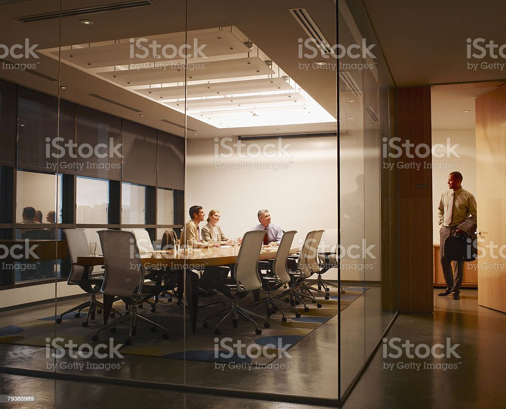 Three businesspeople in boardroom watching businessman leave stock photo
