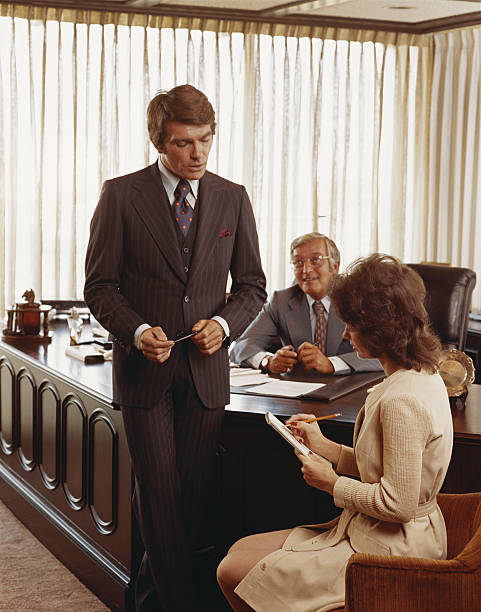 Three businesspeople in office, young woman making notes stock photo