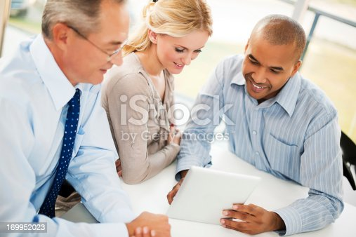 669854210 istock photo Three businesspeople looking on a touchpad. 169952023