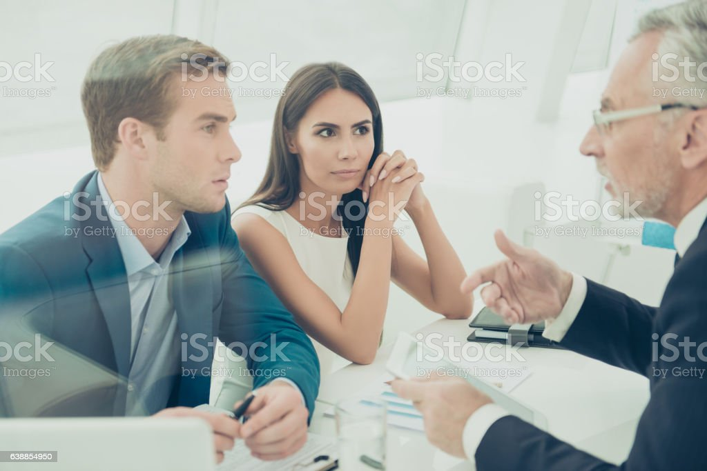 Three businesspeople sitting at office and having business meeting stock photo