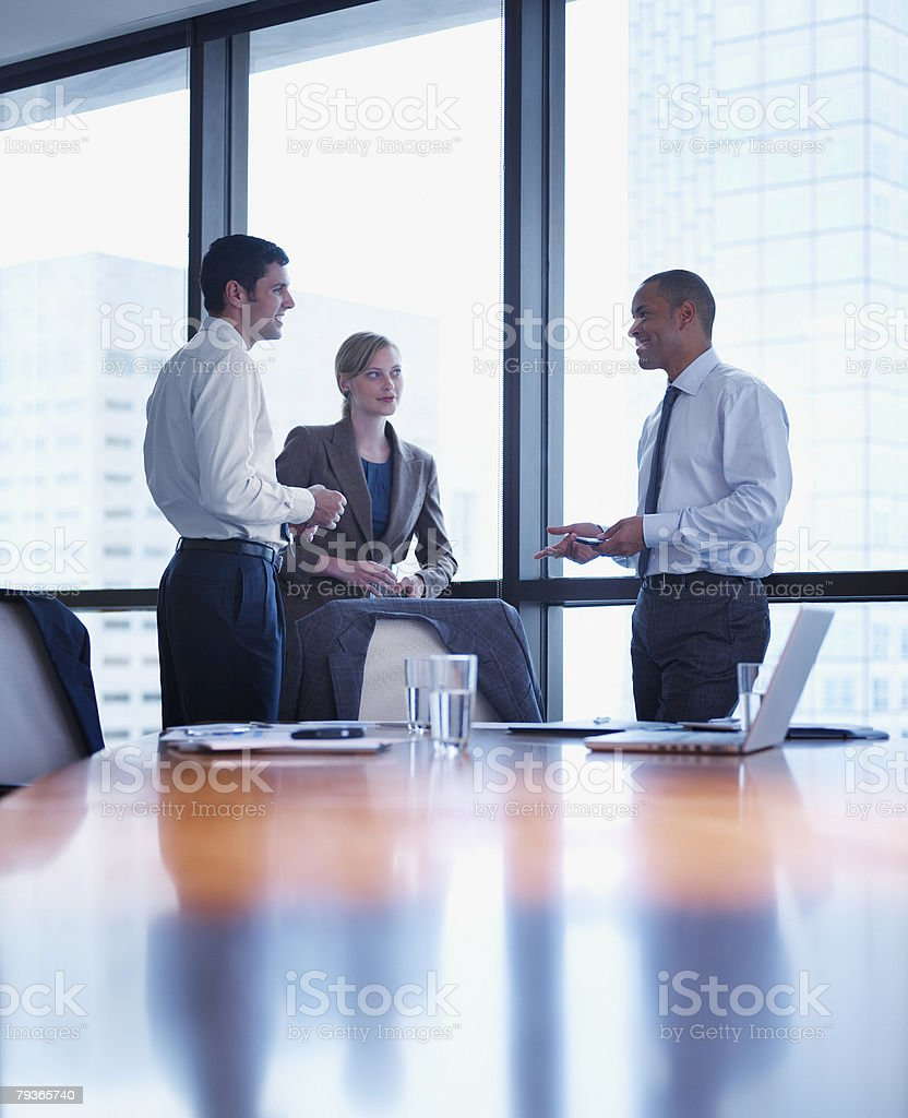Three businesspeople standing in a boardroom stock photo