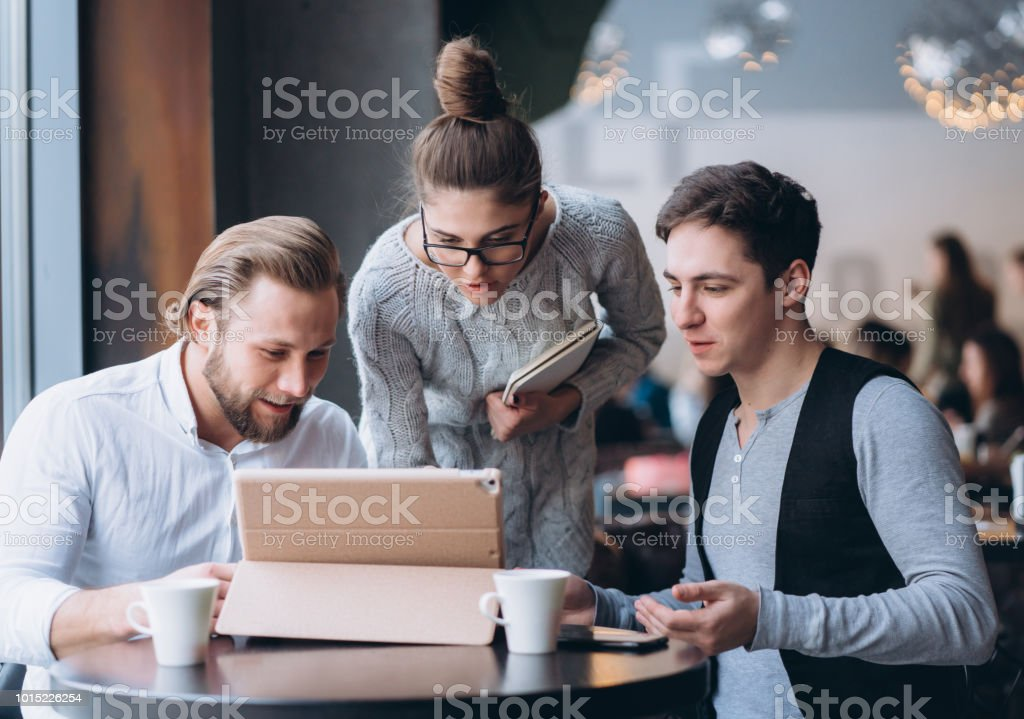 Three Businesspeople Working In cafe stock photo
