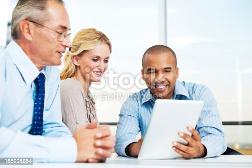 669854210 istock photo Three businesspeople working on a touchpad. 185228654