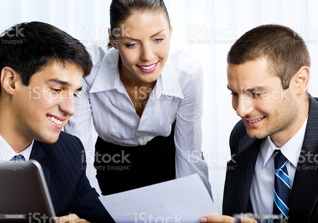Three businesspeople working with document at office royalty-free stock photo
