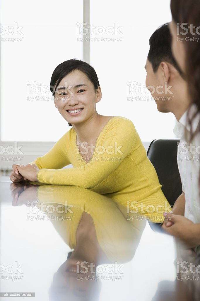 Three businessperson talking at conference table, focus on woman in background Стоковые фото Стоковая фотография