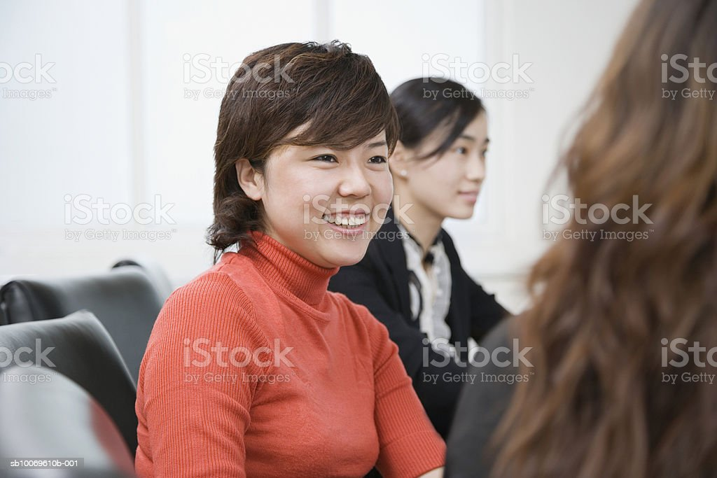 Three businesswomen at conference table, focus on woman smiling, close-up Стоковые фото Стоковая фотография
