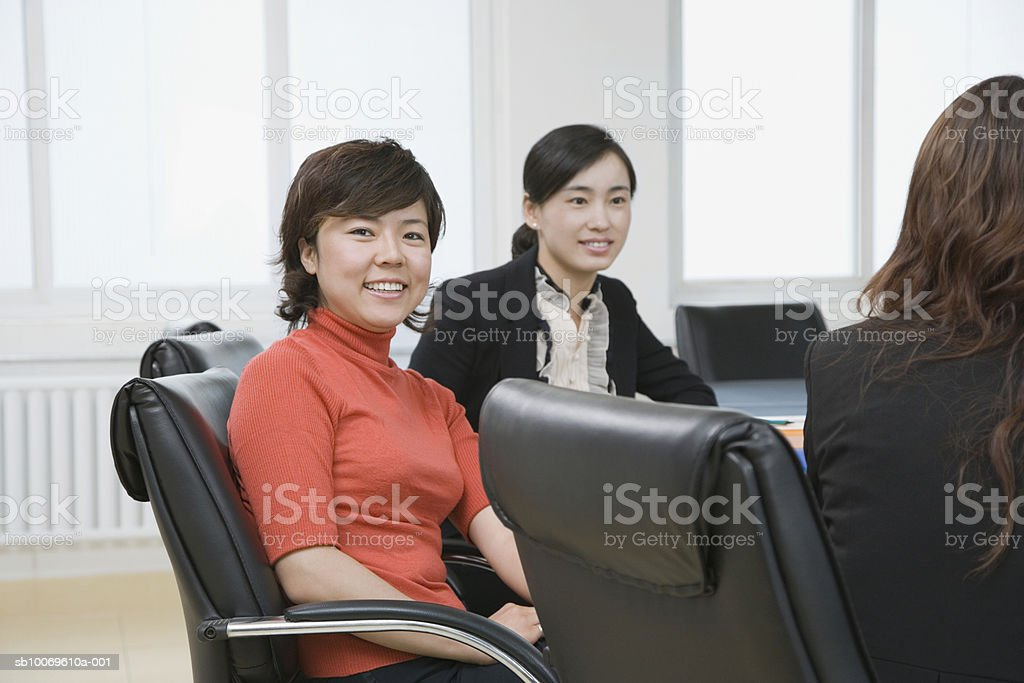 Three businesswomen at conference table, smiling royalty-free stock photo