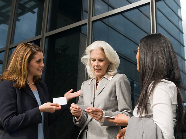 Three businesswomen exchanging business cards outside stock photo
