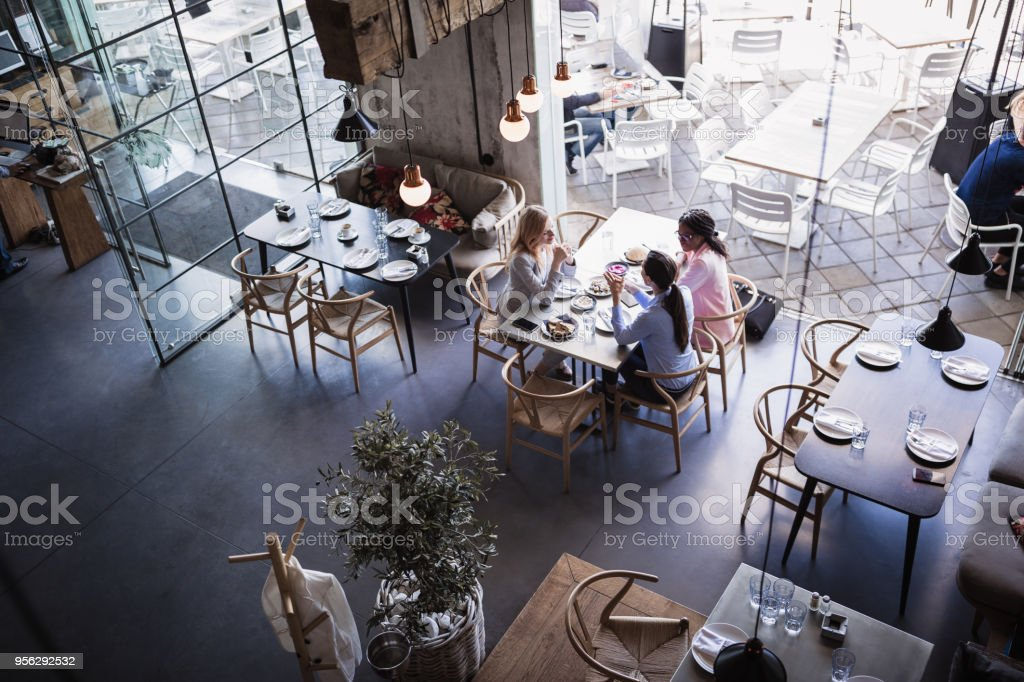 Three businesswomen having meeting and business lunch at high-end restaurant stock photo