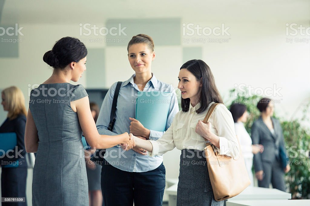 Three businesswomen talking in an office Three businesswomen meeting in a modern office hall, two of them shaking hands. People in the background. 2015 Stock Photo