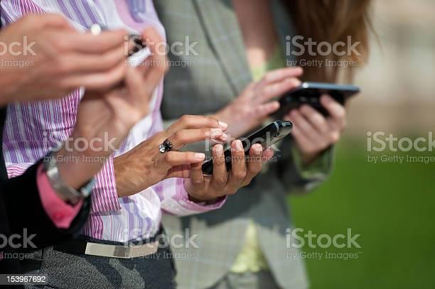 Three Businesswomen Texting Stock Photo - Download Image Now
